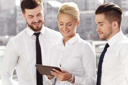 Jonge zakenvrouw met haar partners iets op een digitale tablet