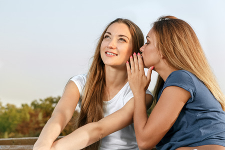 women friendship: Young girl whispering a word in ones ear Stock Photo