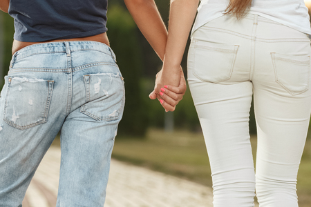people holding hands: Two girlfriends are walking with holding hands in the park Stock Photo