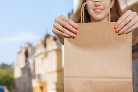 estilo urbano: Young girl holding shopping bag while walking in the city Foto de archivo