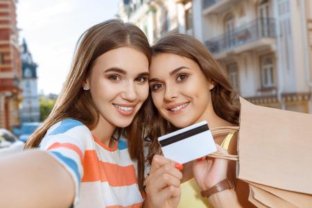 tarjeta visa: Dos ni�as hermosas que hacen autofoto con bolsas de la compra y la tarjeta de cr�dito Foto de archivo