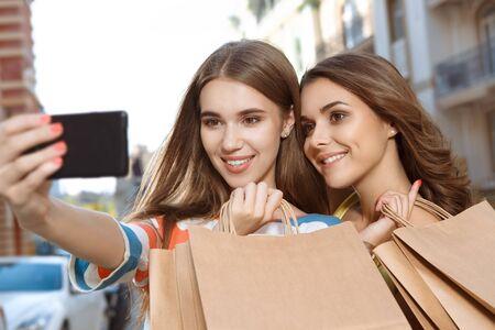 Two beautiful girls doing selfie with shopping bags