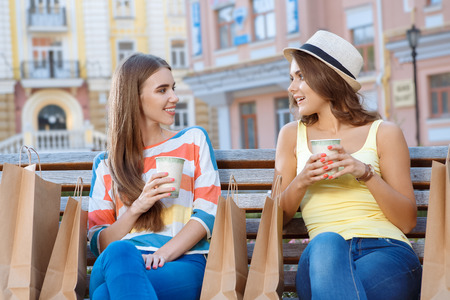 two friends talking: Two friends talking and drinking tea on the bench during shopping