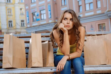 displeasure: Young girl sitting on the bench with shopping bags with displeasure