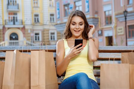 woman bag: Young girl using mobile phone while sitting on the bench with shopping bags