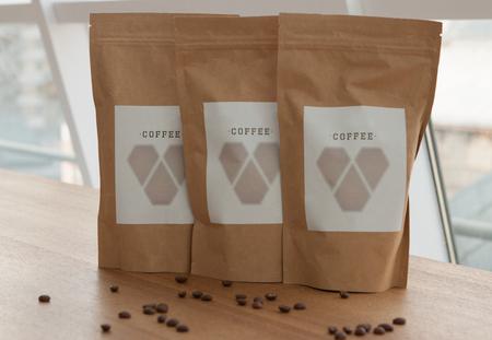 Koffie papieren zak met verkruimelde korrels op een houten tafel Stockfoto