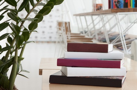 Colorful books are stacked on the table in modern restaurant