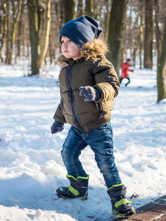 Adorable little boy in winter clothes at winter park background 写真素材