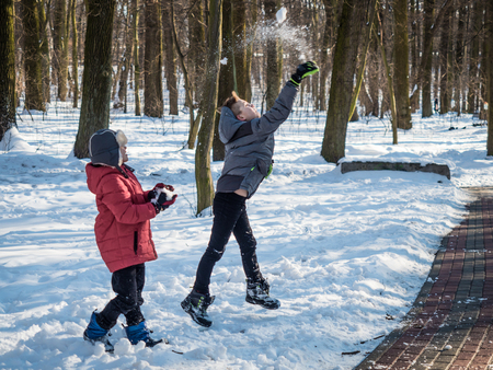 Two little boys throw snow up and have fun in winter park 写真素材