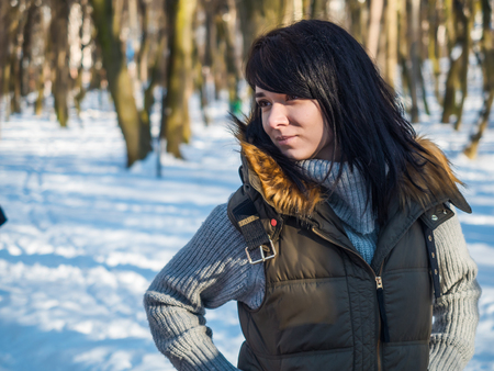Beautiful woman in winter clothes at winter park background