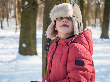 Cute little boy in red jacket at winter park background 写真素材