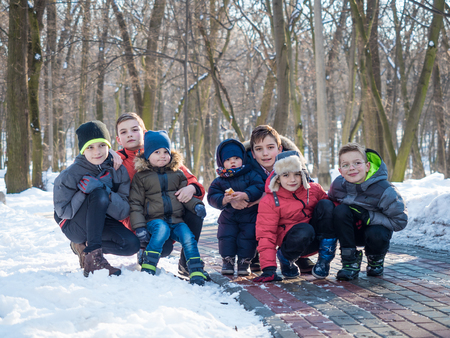 Group of cute little boys posing for camera in winter park 写真素材