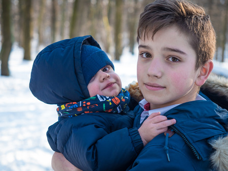 Elder brother hold in arms his young brother at winter park background