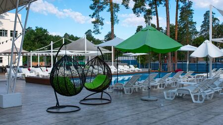 Hanging wicker chairs and swimming pool and parasols at the recreation center in the summer. Concept of recreation and leisure outdoors. Luxury resort.