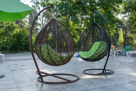 Hanging wicker chairs at the recreation center in the summer. Concept of recreation and leisure outdoors. Luxury resort. 写真素材