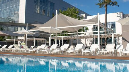 Great summer pool with sunbed and parasols at a country recreation center. Concept of recreation and leisure outdoors. Luxury resort.