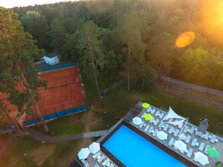 Aerial view beautiful summer pool with sunbed and tennis courts parasols and at a country recreation center. Concept of recreation and leisure outdoors. Luxury resort.