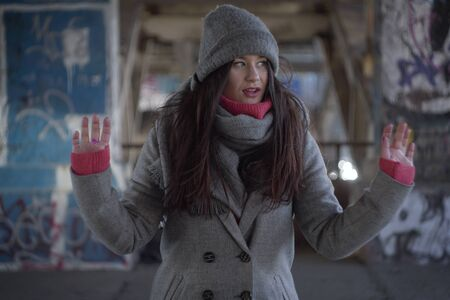 Young Caucasian woman looking aside with mouth open. Portrait of brunette girl with raised hands outdoors.