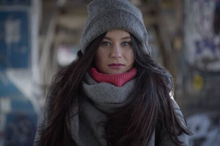 Portrait of beautiful brunette woman looking at camera. Young charming girl standing outdoors on city street in warm hat and scarf. Lifestyle.