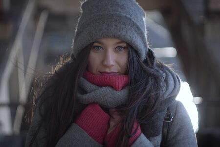 Portrait of freezed Caucasian girl looking at camera. Beautiful brunette woman posing in grey hat outdoors.