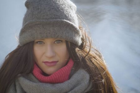 Close-up face of brunette woman in warm grey hat at the background of water. Portrait of pretty Caucasian girl standing outdoors at river bank or lake shore. 版權商用圖片