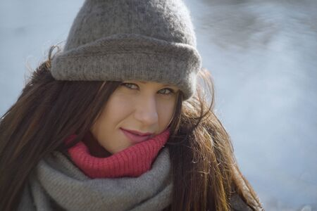 Close-up of pretty smiling Caucasian girl in grey hat and scarf. Portrait of happy brunette woman at the background of autumn river or lake on sunny day. Leisure outdoors, nature, lifestyle. 版權商用圖片