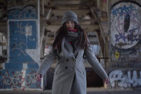 Middle shot of young brunette girl in grey autumn coat standing at the background of walls with graffiti. Urban lifestyle, underground, youth.