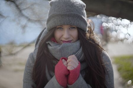 Charming young Caucasian woman holding hands together on sunny autumn day. Portrait of brunette girl in warm clothes looking at camera outdoors.