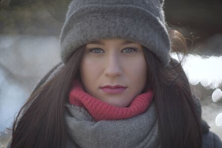 Close-up face of serious Caucasian girl in warm hat and scarf looking at camera. Portrait of young pretty woman outdoors.