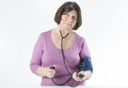arterial: Elderly woman measuring arterial pressure Stock Photo