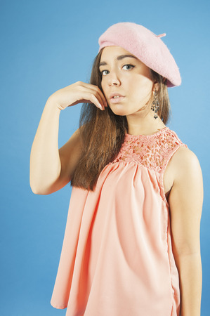 18 years old: Portrait of a young girl in blouse and beret. Studio photography on a blue background. Age 18 years old girl. Stock Photo