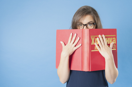 18 years old: Girl with glasses peeping from behind a big book. Studio photography on a blue background. Age 18 years old girl. Stock Photo