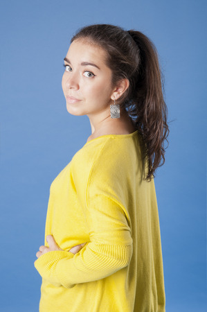 18 years old: Girl in a yellow jacket half-turned. Studio photography on a blue background. Age 18 years old girl.