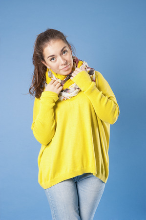 18 years old: Girl in jeans, a yellow jersey and scarf. Studio photography on a blue background. Age 18 years old girl. Stock Photo