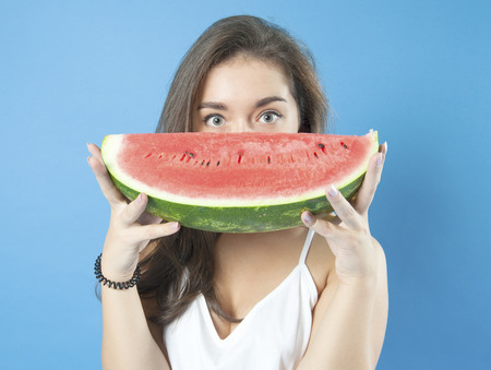 18 years old: Young girl with a slice of ripe watermelon. Studio photography on a blue background. Age 18 years old girl.