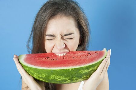 18 years old: Girl biting a slice of watermelon. Studio photography on a blue background. Age 18 years old girl.