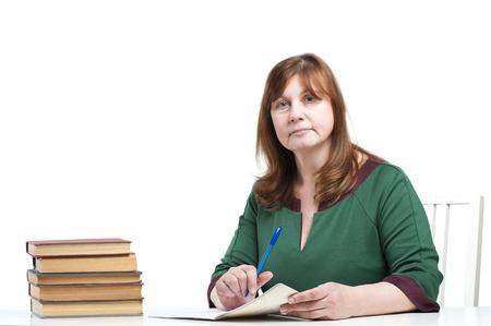 中年の女性教師は、ノートブックをチェックします。 白い背景のスタジオ撮影。