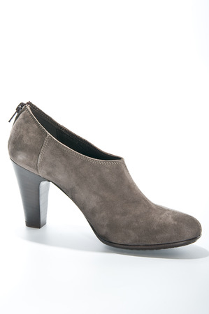 clasp feet: Womens suede ankle boots with high heels. Studio photography on a light background.