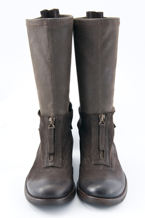 clasp feet: Womens brown leather boots with low heels. Studio photography on a light background.