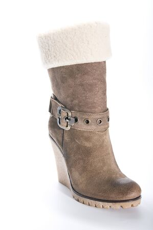 clasp feet: Womens beige suede boots on a high platform sole. Studio photography on a light background.