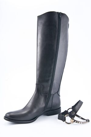 clasp feet: Female black leather boots with low heels. Studio photography on a light background.