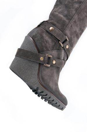 clasp feet: Womens brown suede boots with high wedges (part). Studio photography on a white background under clipping. Stock Photo