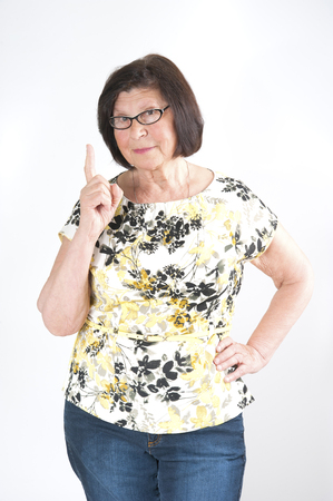 threatens: Attractive elderly woman threatens with a finger. Studio photography on a light gray background.