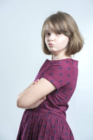 girl in burgundy dress: Portrait of offended girl. Age 10 years. Studio photography on a light gray background.