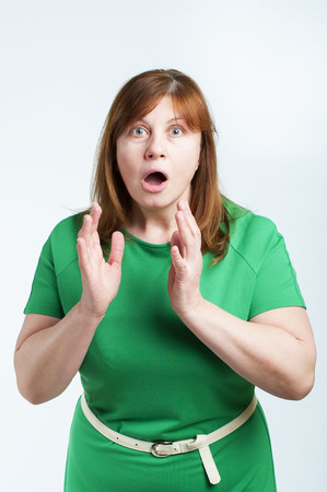 dismayed: Surprised middle-aged woman. Studio photography on a white background (light). Stock Photo