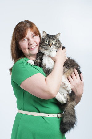 A woman holds a big fluffy cat. Studio photography on a white background (light).