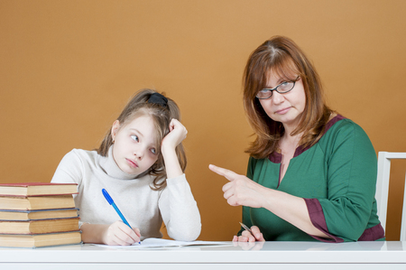 demanding: Strict woman teacher points at student. Studio photography on brown (orange) background.