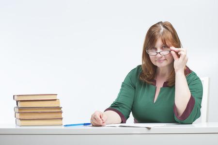 rigor: Woman teacher checks the notebook. Studio photography on brown (orange) background.