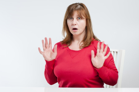 unexpectedness: Frightened middle-aged woman. Studio photography on a light (white) background. Stock Photo