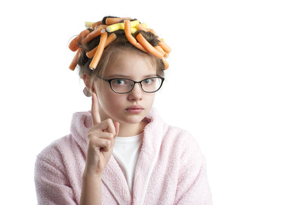 age 10: Girl in curlers and a bathrobe with a raised finger. Studio photography on a white background. Age of child 10 years.